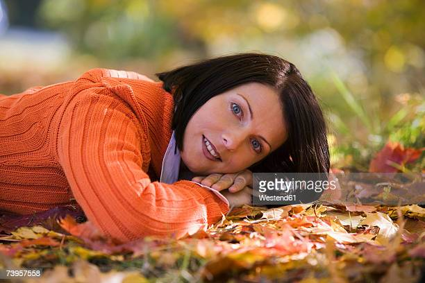 woman lying on autumn leaves, close-up, portrait - mid adult woman sweater stock pictures, royalty-free photos & images
