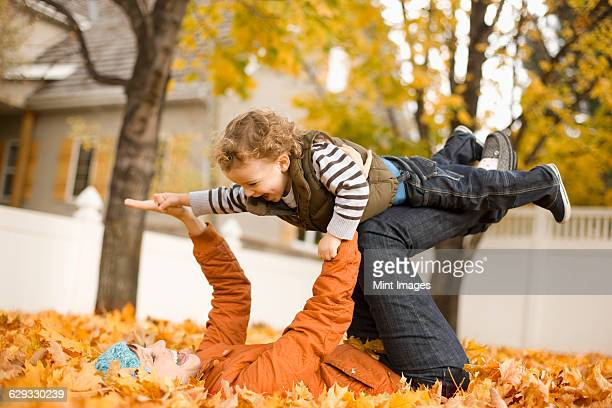 A woman lying on autumn leaves holding a child in the air, balancing on her knees.