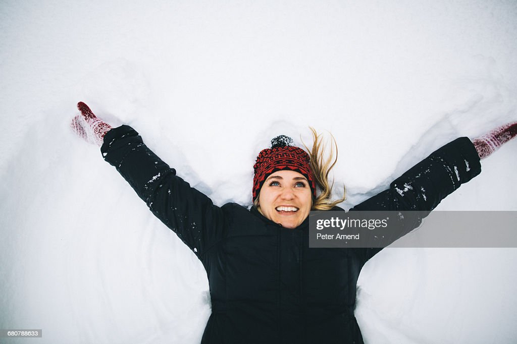 Woman lying on back in snow arms open : Stock Photo