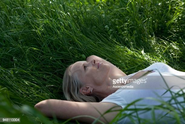 woman lying on back in tall grasses - solo una donna matura foto e immagini stock