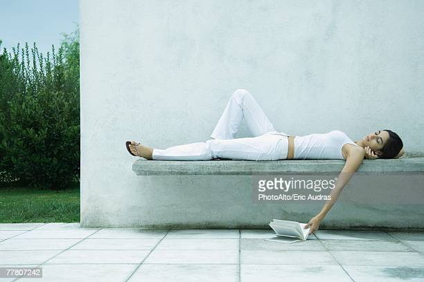 Woman lying on back, letting book fall to ground