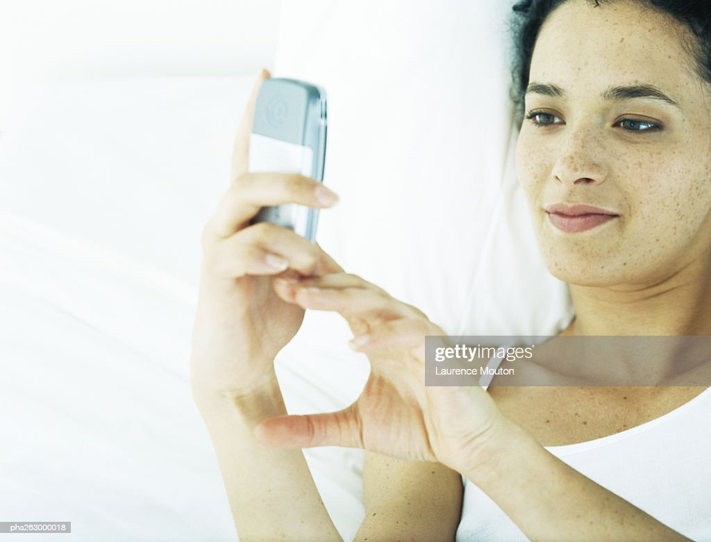 Woman lying on back on bed, looking at cell phone : Stock Photo