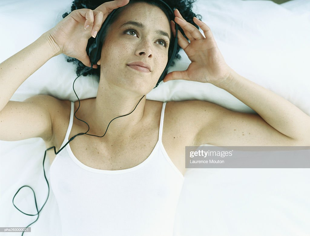 Woman lying on back on bed with earphones on and hands at side of head : Stockfoto
