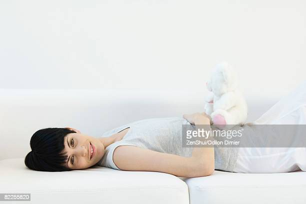 Woman lying on back on sofa, teddy bear sitting on her stomach, smiling at camera