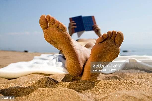 Woman lying on beach, reading book (focus on foreground)
