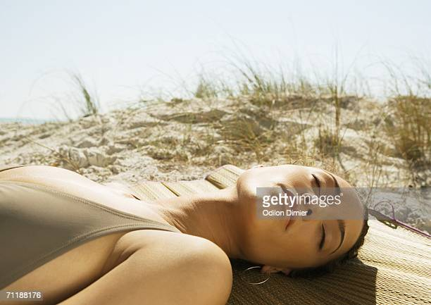 Woman lying on beach, sand dune in background