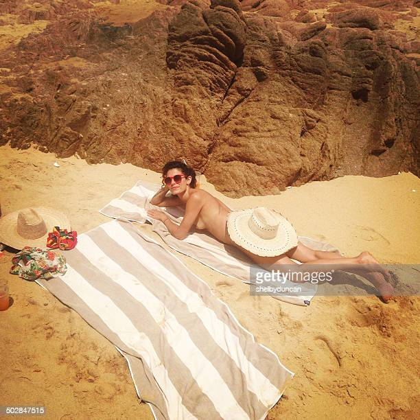 Woman lying on beach with sunhat covering her bottom