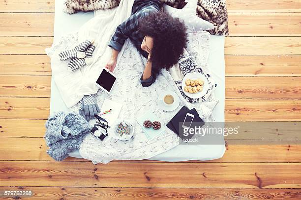 Woman lying on bed and using digital tablet