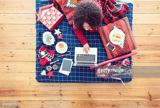 Woman lying on bed and using laptop
