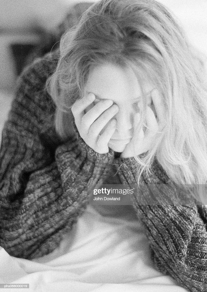 Woman lying on bed, hands on face, black and white. : Stockfoto