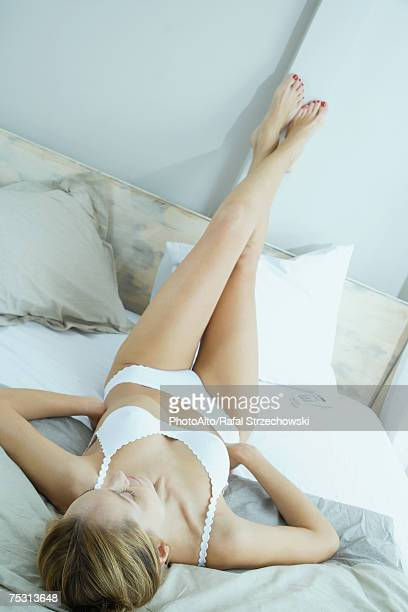 Woman lying on bed in underwear with legs up