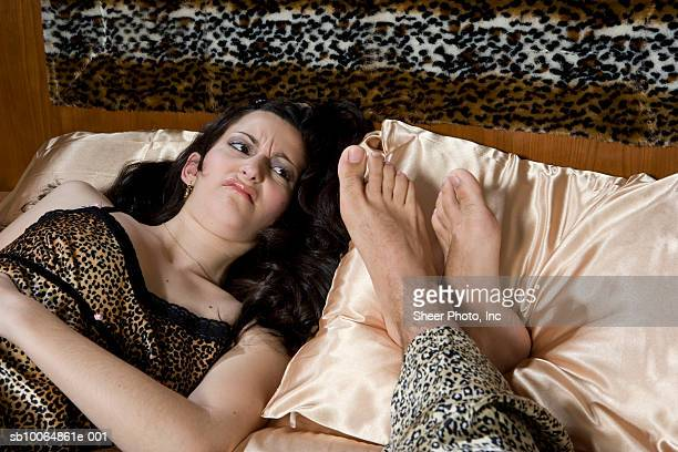 Woman lying on bed, looking at man's feet on pillow