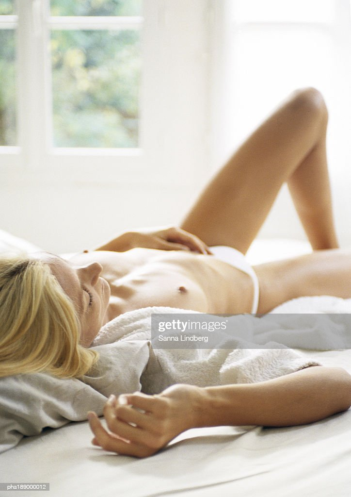 Woman lying on bed, partially nude. : Stockfoto