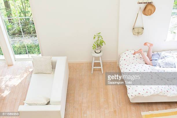 woman lying on bed - tidy room stock pictures, royalty-free photos & images