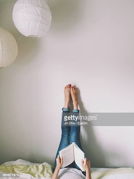 woman lying on bed reading book with legs raised - vertikal stock-fotos und bilder