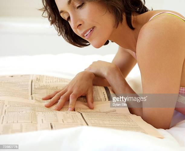 Woman lying on bed reading newspaper, smiling