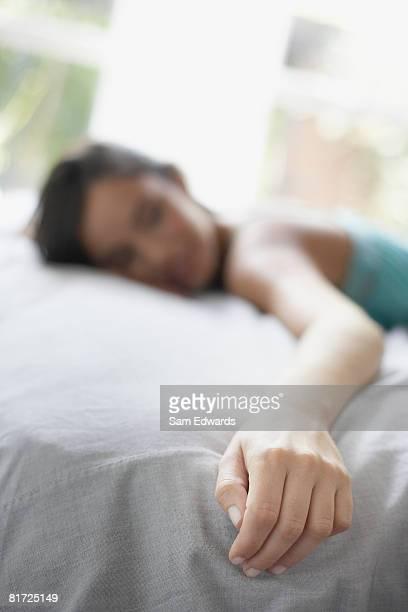 femme allongée sur le lit, se concentrant sur sa main - grand lit photos et images de collection