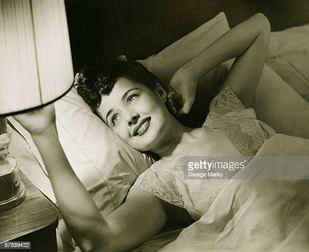 Woman lying on bed, turning off lamp on night table, (B&W), elevated view