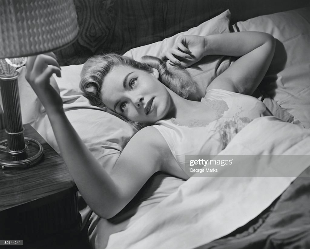 Woman lying on bed turning off lamp, (B&W), : Stock Photo