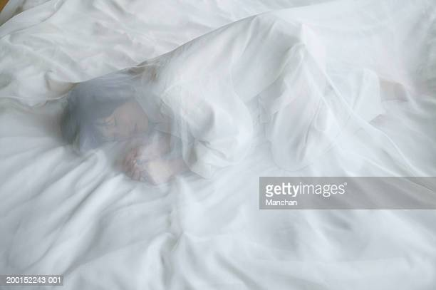 Woman lying on bed, under transparent sheet
