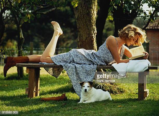 Woman lying on bench by tree reading, dog beneath bench