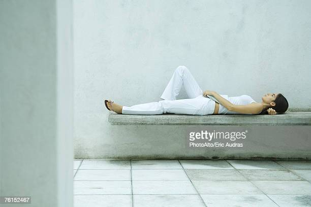 'Woman lying on bench, full length, side view'