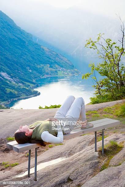 woman lying on bench, river and valley in background - wasserform stock-fotos und bilder