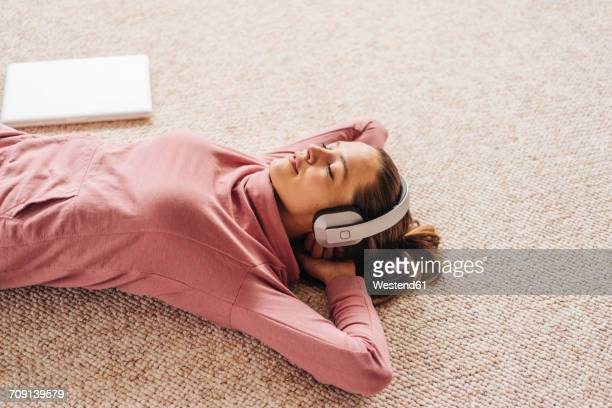 Woman lying on carpet wearing headphones