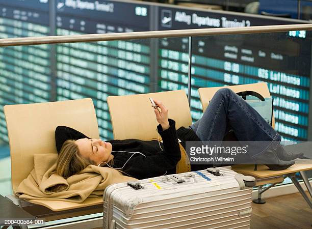Woman lying on chairs in airport waiting area, looking at MP3 player, side view