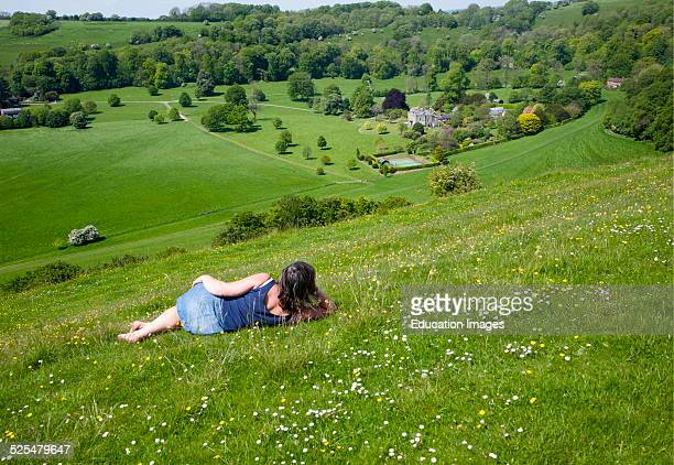 Woman lying on chalk grassland looking into deep green valley containing Rainscombe House Oare Hill Wiltshire England