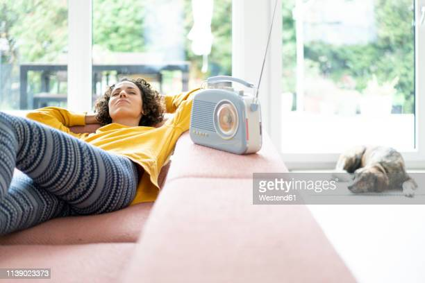 woman lying on couch listening to music with portable radio at home - radio stock pictures, royalty-free photos & images