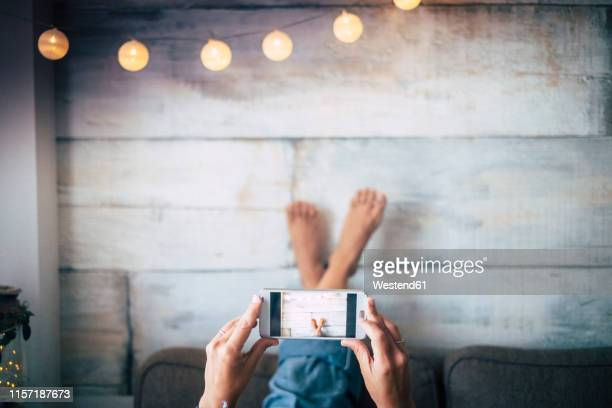Woman lying on couch taking a cell phone picture of her feet