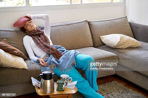 Woman lying on couch with hot-bag water on head