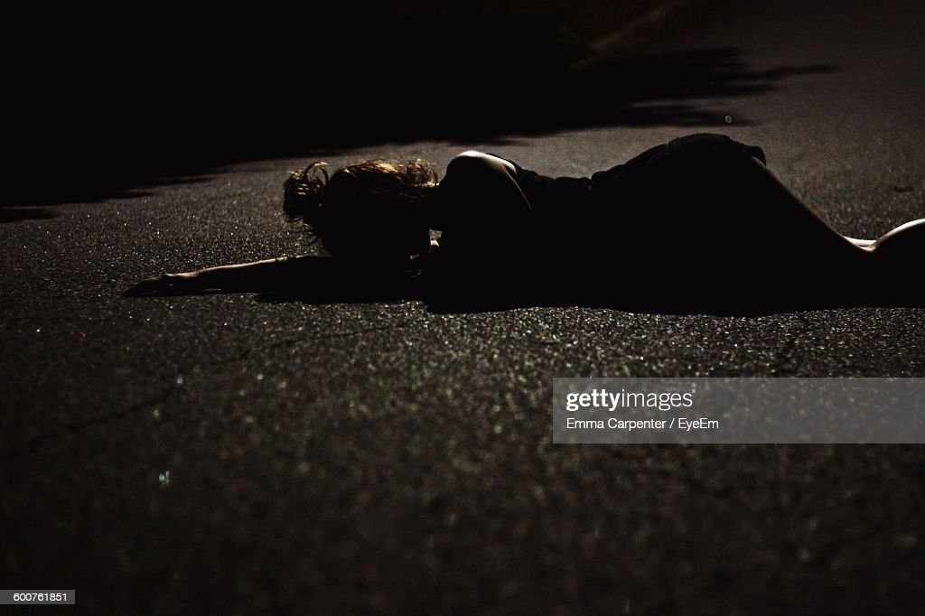 Woman Lying On Country Road At Night : Stock Photo