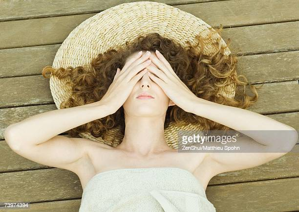 Woman lying on deck, wrapped in towel, head on mat, hands over eyes