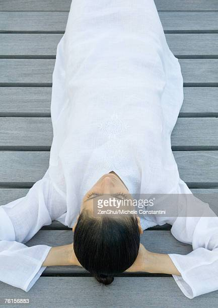 Woman lying on decking, hands behind head, high angle view