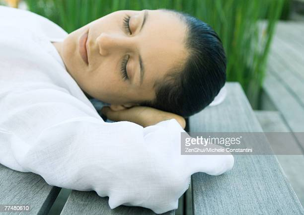 Woman lying on decking, hands behind head