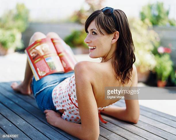 Woman Lying on Decking in a Garden With an Open Magazine on her Lap