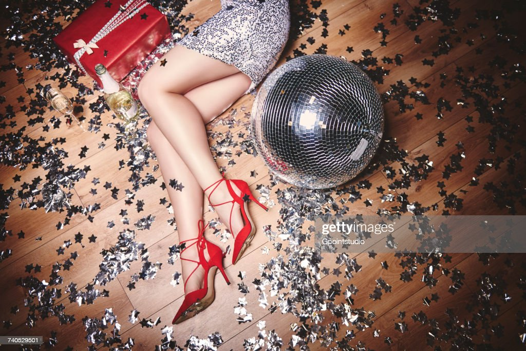 Woman lying on floor at party, surrounded by glitter, champagne bottle and disco ball, overhead view : Stock Photo