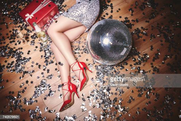 Woman lying on floor at party, surrounded by glitter, champagne bottle and disco ball, overhead view