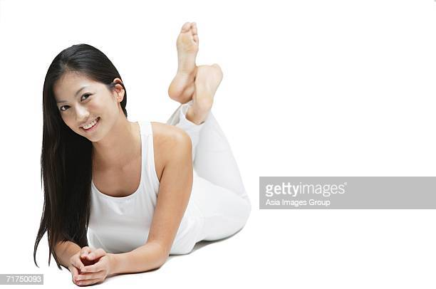 woman lying on floor, legs crossed at the ankle, smiling at camera - soles pose stock pictures, royalty-free photos & images