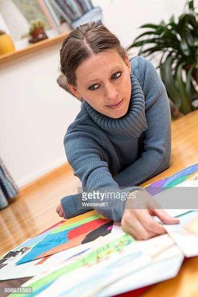 Woman lying on floor looking at childrens paintings