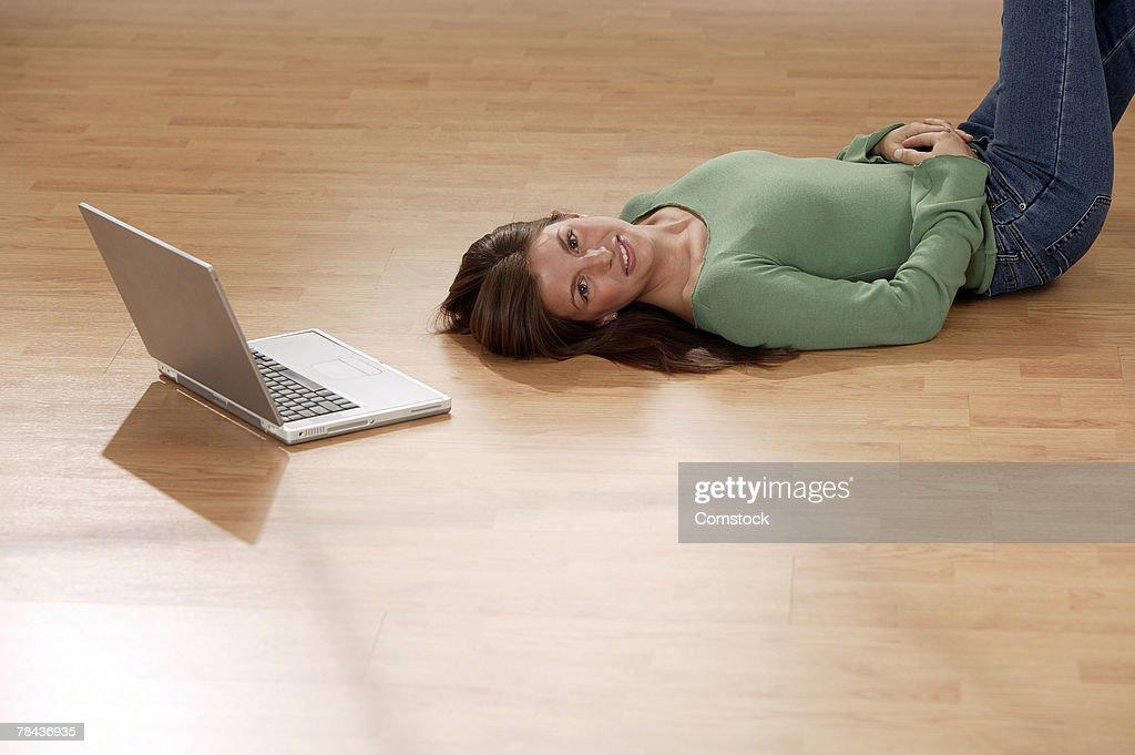 Woman lying on floor next to laptop computer : Stockfoto