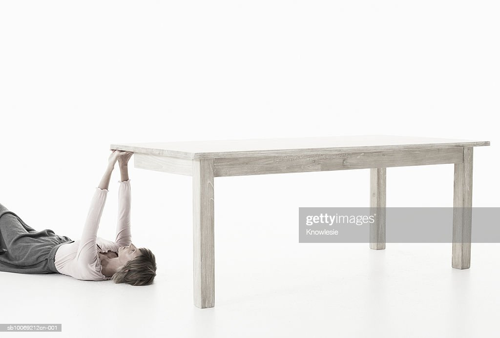 Woman lying on floor supporting one corner of table against white background : Stockfoto