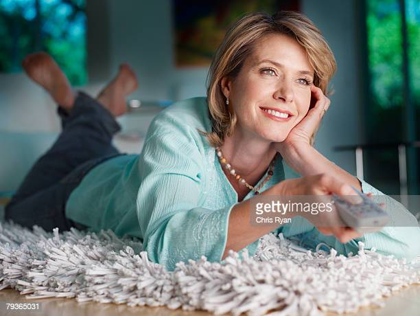 Woman lying on floor watching television