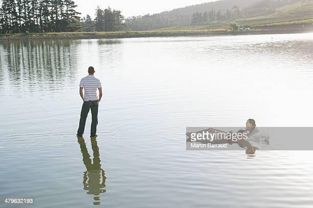 mulher deitada no dispositivo de flutuação e homem de pé na água - homem moreno imagens e fotografias de stock