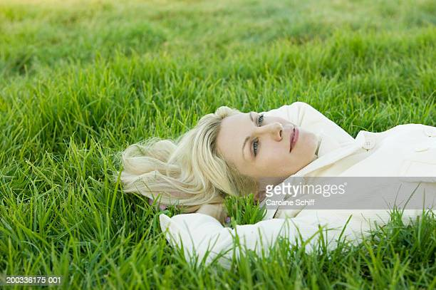 woman lying on grass, hands behind head, side view - schiff stock photos and pictures