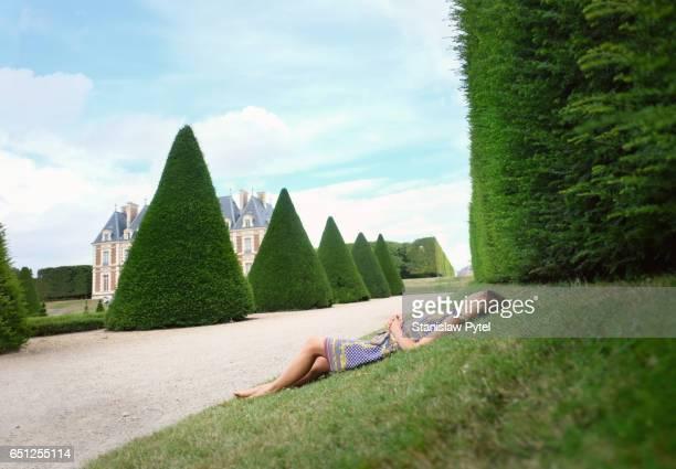 woman lying on grass in park - トピアリー ストックフォトと画像