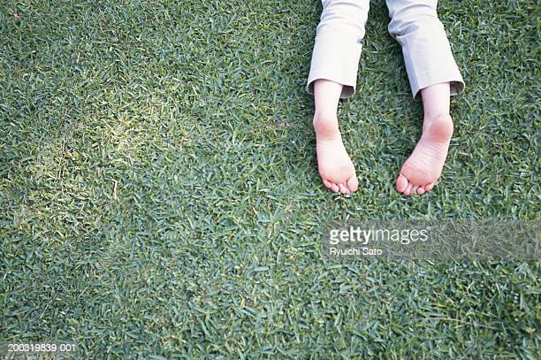 woman lying on grass, low section - woman lying on stomach with feet up stock photos and pictures