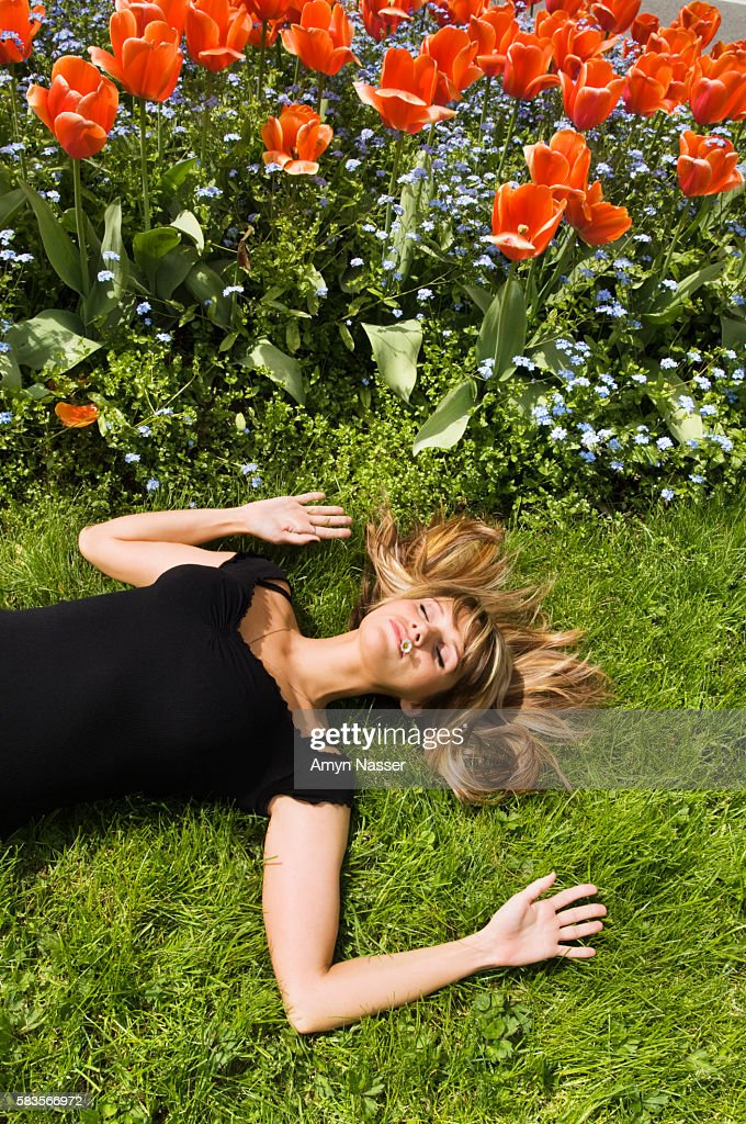 Woman lying on grass near flowers : Stock Photo